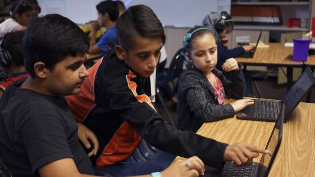 In this Tuesday, Oct. 4, 2016 photo, student Abdullah Arab, middle, 11, helps classmates Habeebullah Najme, left, 12, and Nada Alradi, right, 11, in a room filled with refugee children at Cajon Valley Middle School in El Cajon, Calif. According to the U.S. State Department, nearly 80 percent of the more than 11,000 Syrian arrivals over the past year were children. Many of those children are enrolling in public schools around the country, including Chicago; Austin, Texas; New Haven, Connecticut; and El Cajon, which received 76 new Syrian students the first week of school. (AP Photo/Christine Armario)