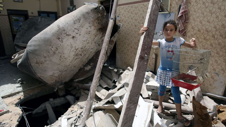A Palestinian girl stands in the ruins of her home