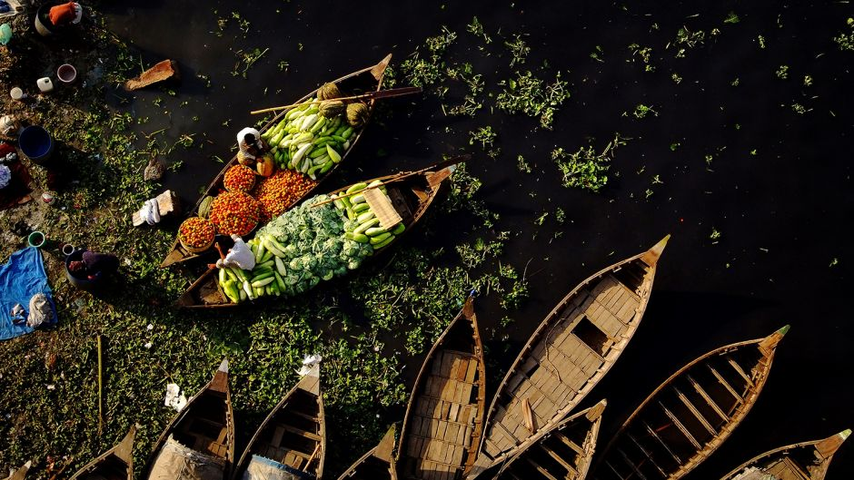 Over the black waters of the Buriganga, merchants unload shipments of fresh produce destined for city markets. Photo: Daniel Lanteigne. Creative Commons BY-NC-ND.