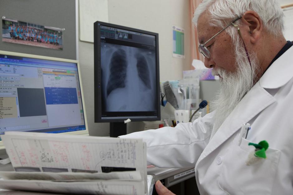 Dr Masaaki Shimanuki checks patient records in his office at Iwate Prefectural Takata hospital in Rikuzentakata. Photograph © Kazuma Obara/The Guardian