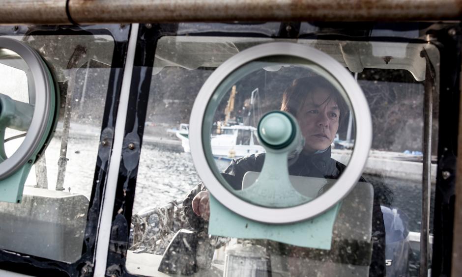 Scallop fisherman Jun Sasaki behind the helm of his boat. Photograph © Kazuma Obara/The Guardian