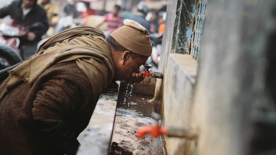 A man drinks from a public water tap in Delhi, India