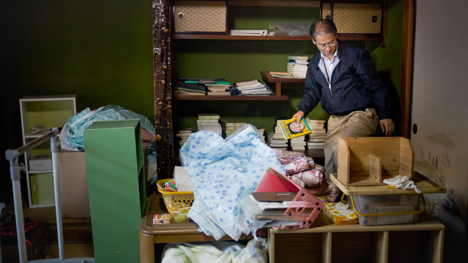 Mr Masakazu Shinkai visiting their abandoned home in Katsurao village in Fukushima prefecture. They had to leave many belonings behind, including most of Mr. Shinkai's books.