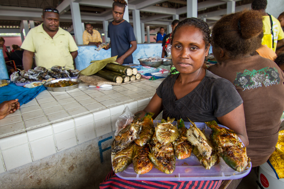 A woman holds cooked reef fish for sale at her stall in Auki market, Malaita Province, Solomon Islands, Photo: Filip Milovac / WorldFish, Creative Commons BY-NC-ND 2.0