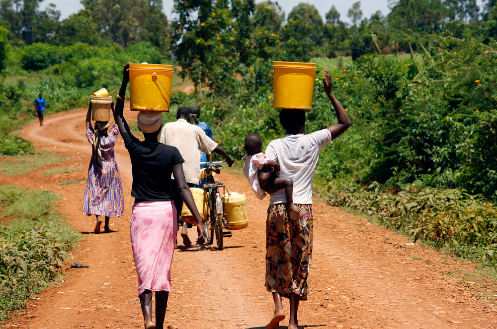 Women in Nyanza province, Kenya, walk each day to collect water for cooking, drinking and cleaning. Photo by Peter Bregg.