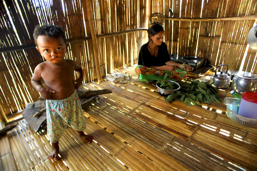 A mother prepares fresh food from the orchards for her family, on a simple cooking stove. The destruction of surrounding primary forest means the diversity of available food stocks is gradually becoming more limited.