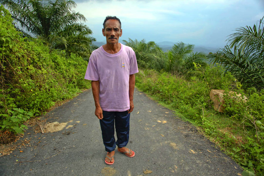 An Orang Asli man stands on the incomplete road that leads to the current village through surrounding palm oil plantations, with the site of his community's previous village somewhere in the background.