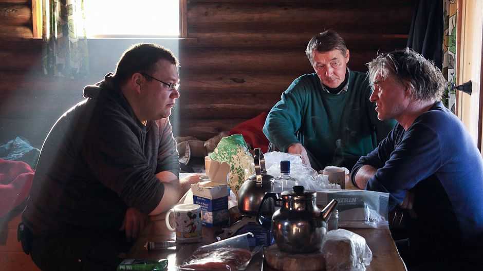 Over breakfast at Jouko Moshnikoff's cabin, Tero Mustonen, Illep Jefremoff, and Vladimir Feodoroff (left to right) mull over the next steps in their climate change adaptation project. Photo: © Gleb Raygorodetsky 2012.