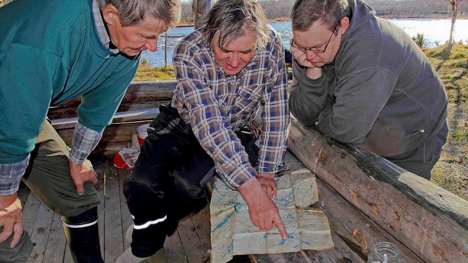 On the porch of Jouko Moshnikoff's cabin — against the backdrop of one of the most significant spawning sites for Atlantic salmon on the Näätämö River — Illep Jefremoff, Vladimir Feodoroff and Tero Mustonen (left to right) examine the area map of the region. Photo: © Gleb Raygorodetsky 2012.