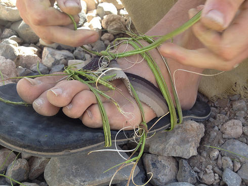 Fixing a busted flip flop on a hike with Yucca. Photo courtesy of HolyScrap.