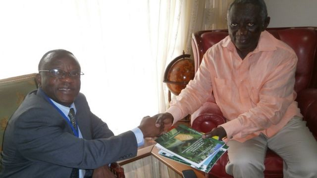UNU-INRA Director, Dr. Elias T. Ayuk (left), presents the institute's latest research reports on climate change and other related areas to Former President John Agyekum Kufuor of Ghana (right).