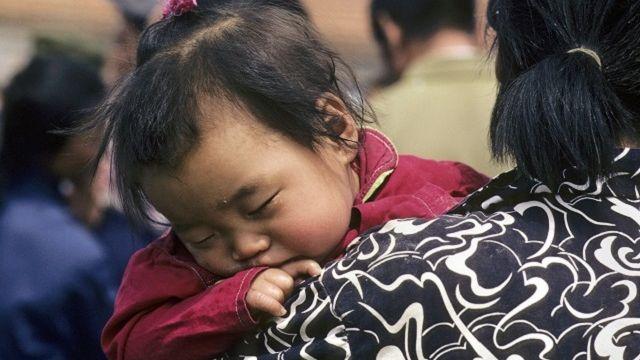 Child sleeping on mother's shoulder in a Beijing park.