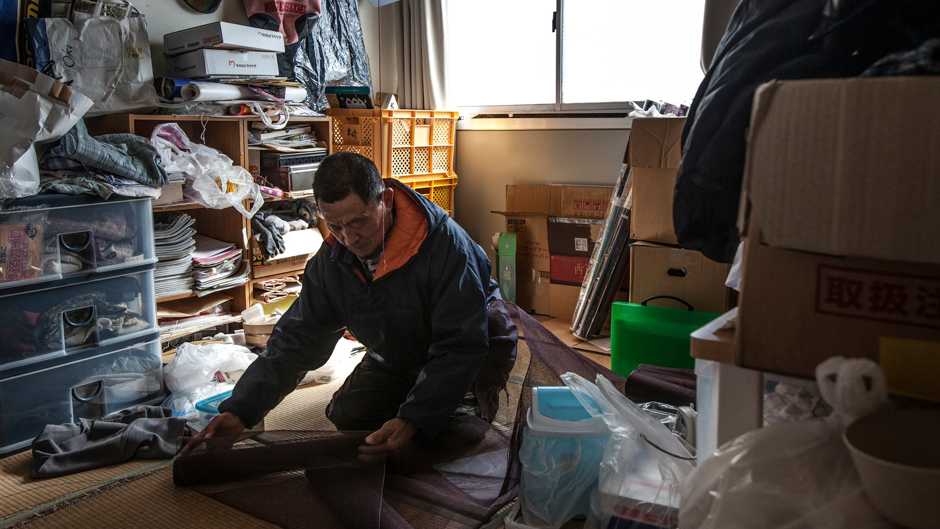 Fisherman Kichiro Sato in the temporary home he shares with son Kazuo, who left the sea after the tsunami to help lead their community's recovery. Photograph ©  Kazuma Obara/The Guardian