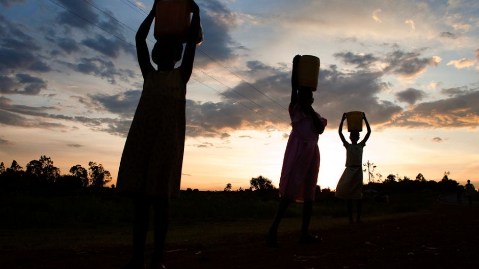 Children carry water from the Awache Seme river in Bondo area of Nyanza province, Kenya. Photo by Peter Bregg.