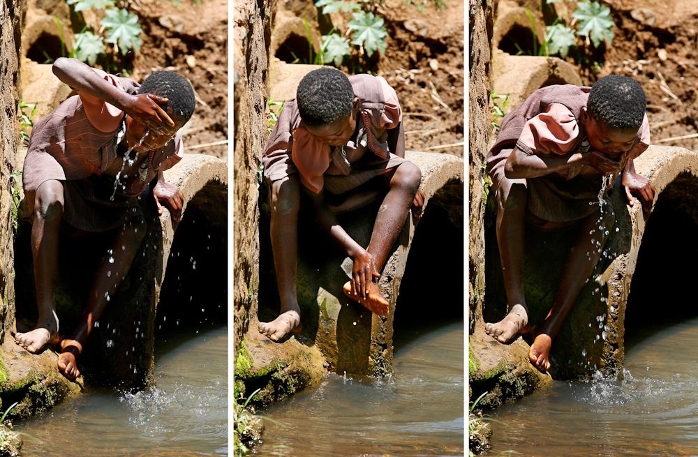 young girl stops at a creek near Kisumu in Kenya to wash her feet ...