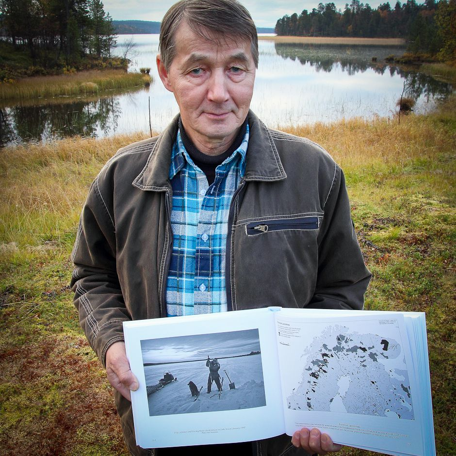 In front of his house on the shore of Lake Sevettijärvi, Illep Jefremoff holds the Eastern Sámi Atlas open to the page with a picture of himself and his dog Kepu, checking fishing nets in the winter of 1993. Photo: © Gleb Raygorodetsky 2012.